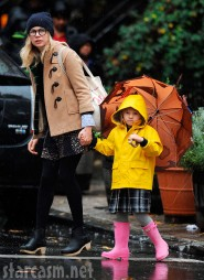 Matilda Ledger in a yellow raincoat, pink boots and toting an umbrella