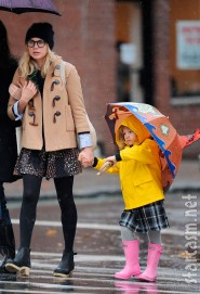 Michell Williams and Matilda Lledger walk to school in the rain