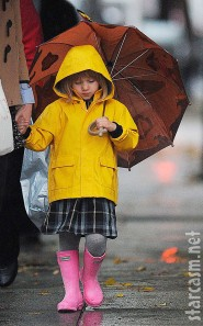 Matilda Ledger sports a yellow raincoat and totes an umbrella in the rain
