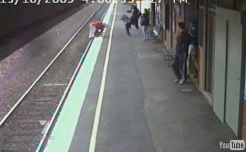 Video still of a baby in a baby carriage falling in front of a train