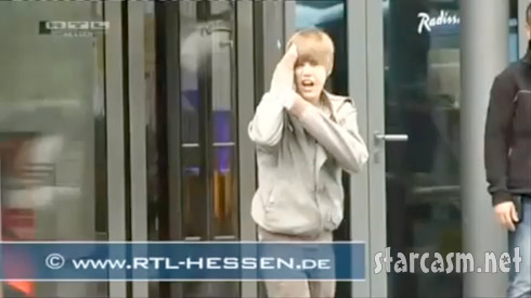 Justin Bieber bangs his head on a revolving door