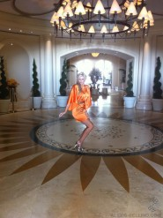 Alexis Bellino models a sexy orange dress for her new fashion line Alexis Couture