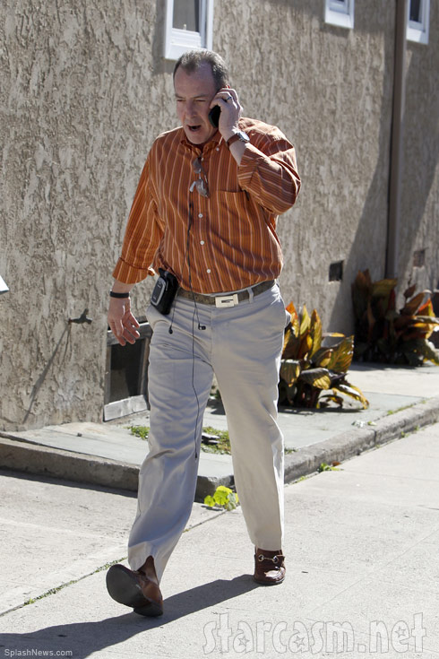 Michael Lohan walking and talking angrily into a cell phone