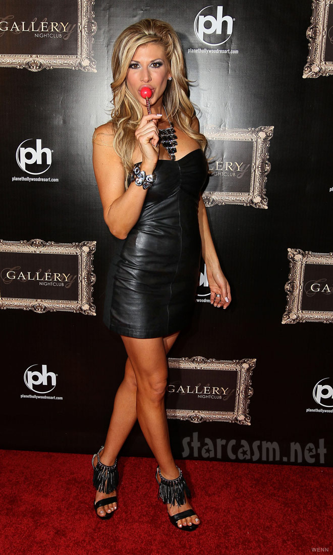 Alexis Bellino wearing leather and sucking on a red lollipop