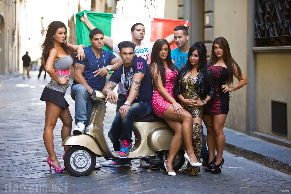 The cast of Jersey Shore pose for a Season 4 promotional photo with an Italian flag and a Vespa scooter