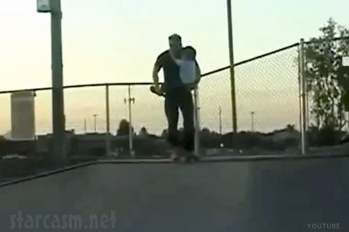 Video of a dad carrying his toddler son while skateboarding down a ramp