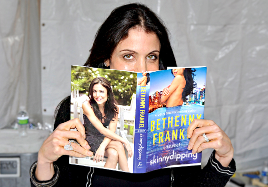 Bethenny Frankel reads a copy of her novel Skinnydipping