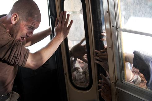 Shane (Jon Bernthal) trapped inside school bus by zombies in The Walking Dead