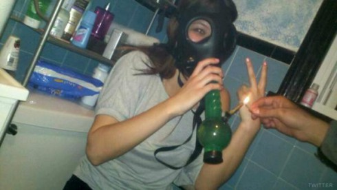 Jo Rivera's girlfriend wearing a gas mask and about to smoke from a bong