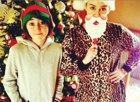Miley Cyrus poses in leopard onesie on Christmas