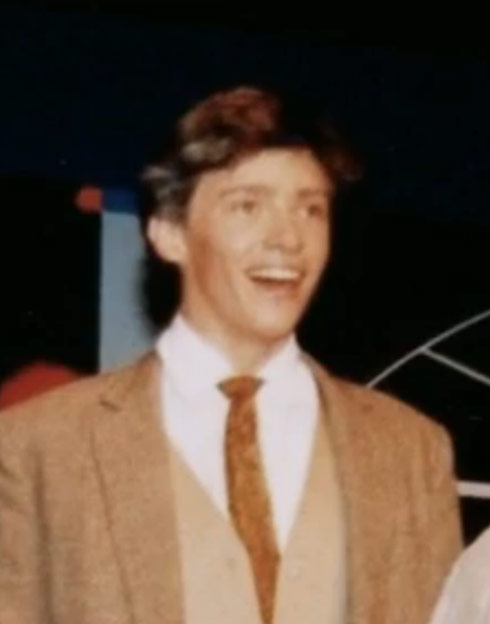 A younger Hugh Jackman on stage at school
