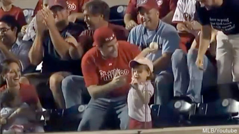A Dad watches as his daughter throws a foul ball back on the field during a Philadelphia Phillies game