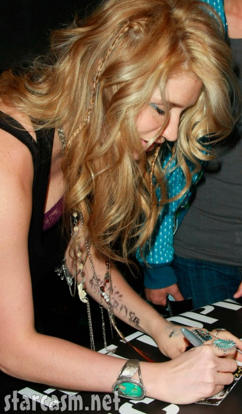 Ke$ha reveals a purple bra and a phone number on her arm
