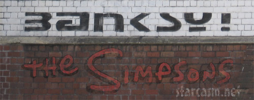 Banksy Graffiti and Simpsons logo on a brick wall