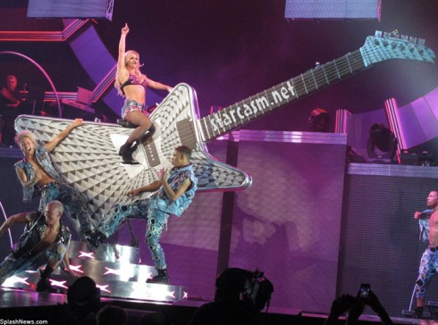 Brit-Brit mounts a giant guitar during the Femme Fatale Tour opener