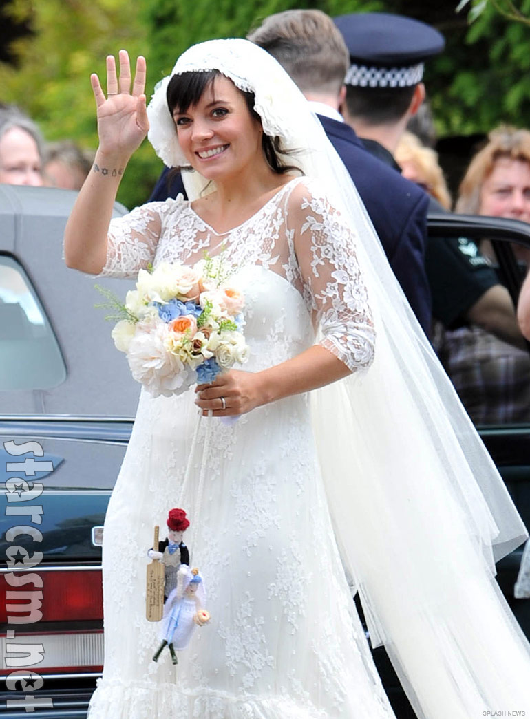 Lily Allen waves to photographers in a beautiful wedding dress designed by Delphine Manivet