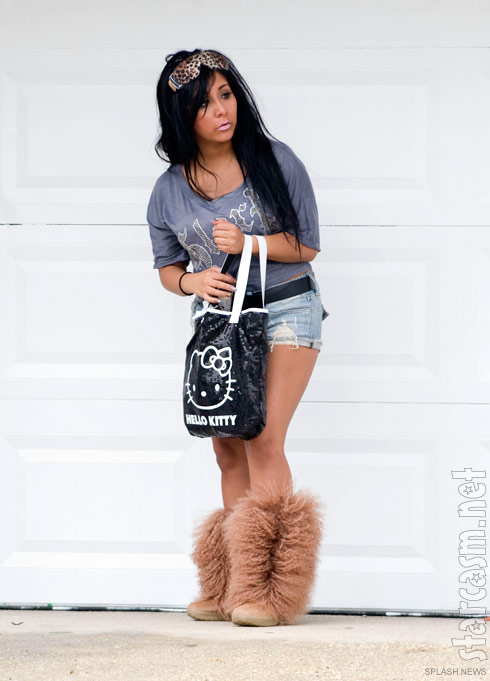 Snooki poses with her Hello Kitty bag in front of a garage door