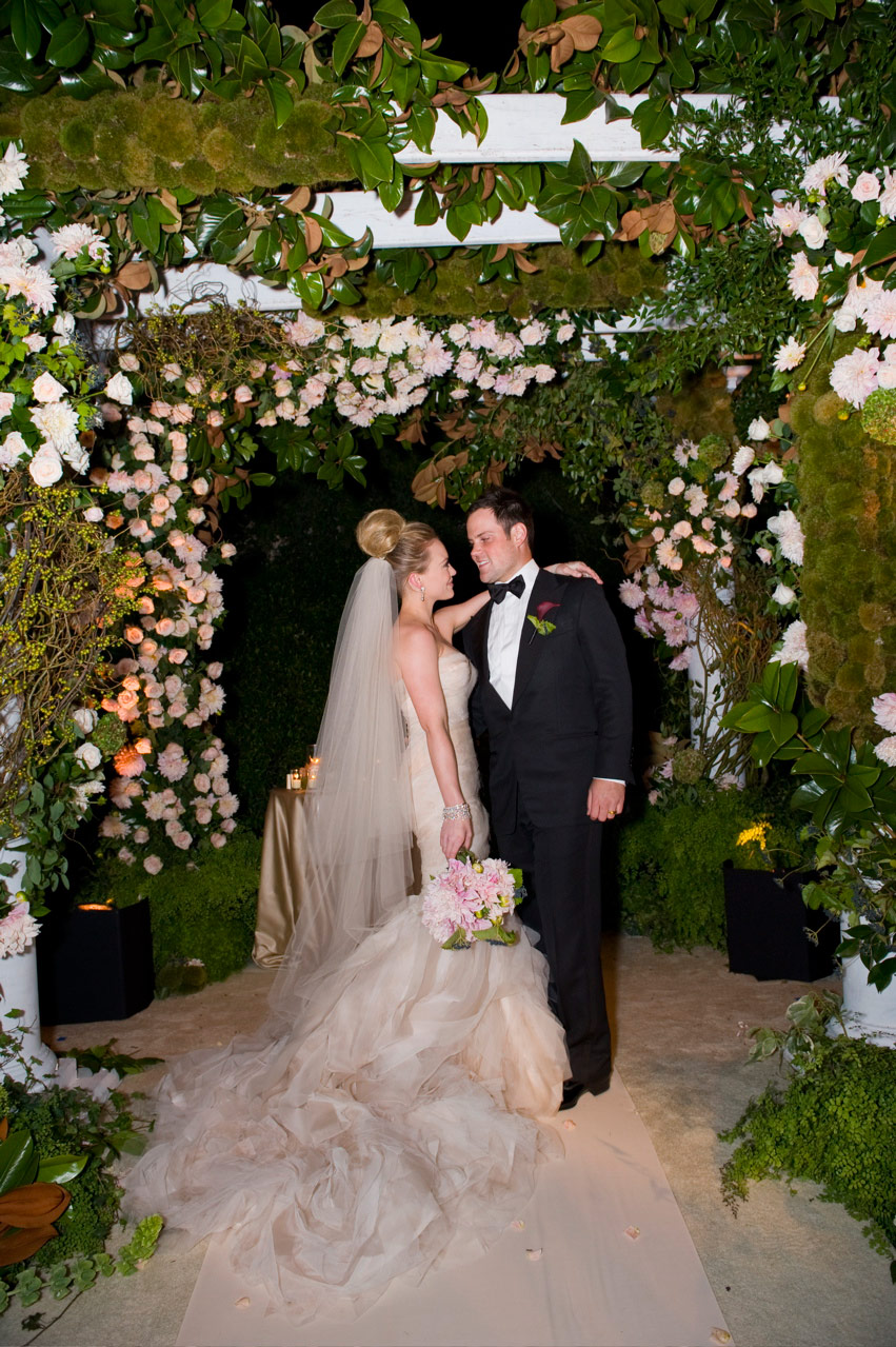 Hilary Duff and Mike Comrie wedding picture featuring the couple under a flowery trellis