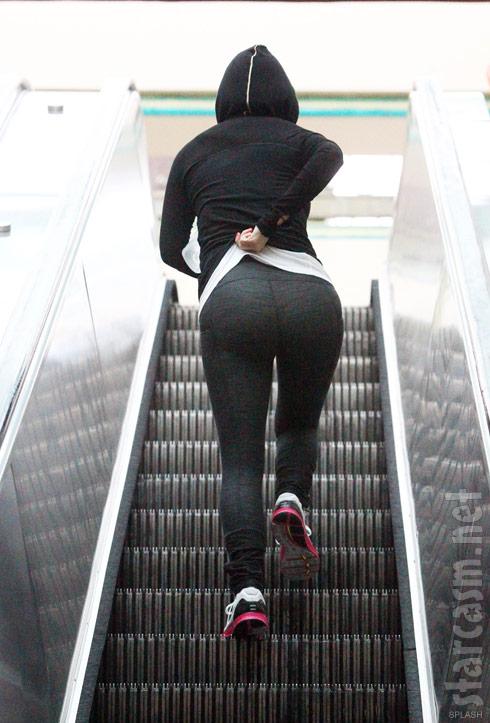 Kim Kardashian booty ascending an escalator