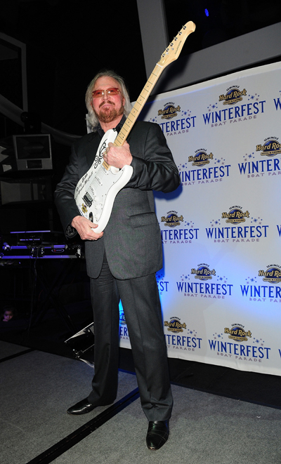 Barry Gibb holds guitar for Winterfest charity