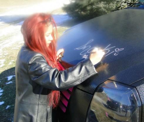 Snooki signs an autograph on her Cadillac Escalade