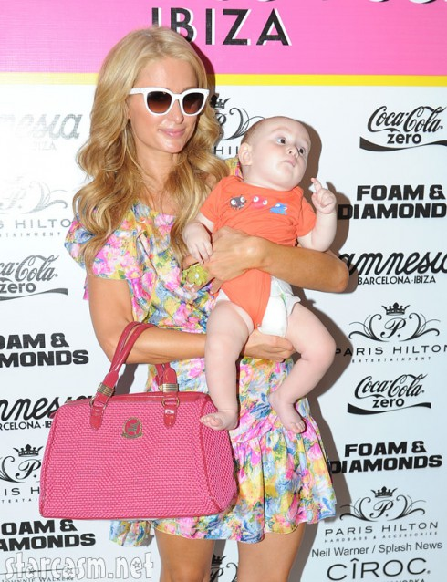 Paris Hilton holds a baby in Ibiza