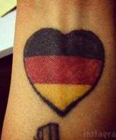 Tosca Yeager German flag heart tattoo wrist