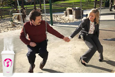 Parks and Rec Ron and Leslie holding hands on the swing
